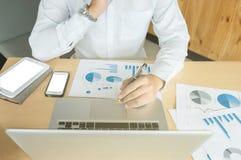 Uomo di affari che lavora all'ufficio con il computer portatile, la compressa ed i documenti fotografia stock