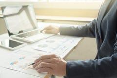 Uomo di affari che lavora all'ufficio con il dat del computer portatile, della compressa e del grafico immagini stock libere da diritti