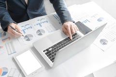 Uomo di affari che lavora all'ufficio con il dat del computer portatile, della compressa e del grafico immagini stock