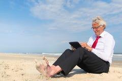 Uomo di affari che lavora alla compressa alla spiaggia Immagini Stock Libere da Diritti