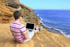 Uomo di affari che lavora alla spiaggia con un computer portatile Fotografia Stock Libera da Diritti