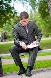 Uomo di affari che lavora con i documenti alla sosta. Allievo Immagini Stock Libere da Diritti
