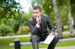 Uomo di affari che lavora con i documenti alla sosta. Allievo Fotografie Stock Libere da Diritti