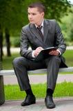 Uomo di affari che lavora con i documenti alla sosta. Allievo Immagini Stock