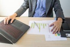 Uomo di affari che lavora con il computer portatile ed i documenti sulla tavola di legno Immagini Stock Libere da Diritti