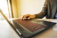 Uomo di affari che lavora con il computer portatile ed i documenti sulla tavola di legno Fotografia Stock