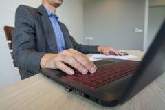Uomo di affari che lavora con il computer portatile ed i documenti sulla tavola di legno Fotografie Stock