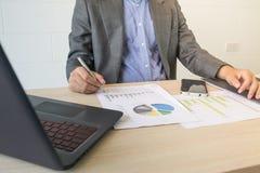 Uomo di affari che lavora con il computer portatile ed i documenti sulla tavola di legno Fotografia Stock Libera da Diritti