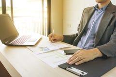 Uomo di affari che lavora con il computer portatile ed i documenti sulla tavola di legno Fotografie Stock Libere da Diritti