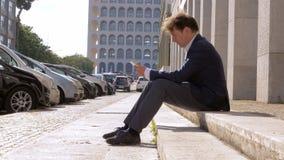 Uomo di affari che lavora con la compressa che si siede sulla via in città stock footage