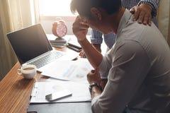 Uomo di affari che lavora con lo sforzo all'ufficio con il computer portatile ed il documento Immagini Stock