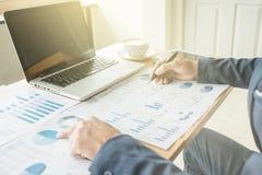 Uomo di affari che lavorano all'ufficio con il computer portatile e grafico finanziario fotografia stock libera da diritti