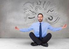 Uomo di affari che medita contro la parete grigia con i grafici della freccia Fotografia Stock