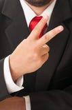 Uomo di affari che mostra numero due o il segno di pace Immagine Stock Libera da Diritti