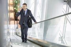 Uomo di affari che parla sul telefono cellulare mentre sulla scala mobile Fotografie Stock