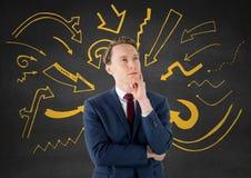 Uomo di affari che pensa contro la parete grigia con i grafici gialli della freccia Immagini Stock