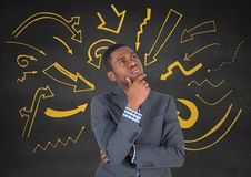 Uomo di affari che pensa contro la parete grigia con i grafici gialli della freccia Immagine Stock Libera da Diritti