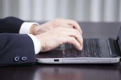 Uomo di affari che per mezzo del computer portatile Fotografia Stock