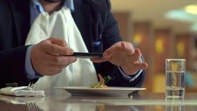 Uomo di affari che per mezzo del telefono cellulare e producendo l'alimento della foto nel ristorante archivi video