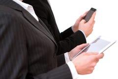 Uomo di affari che per mezzo della compressa e dello smartphone Fotografia Stock