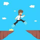 Uomo di affari che per mezzo della molla dei piedi, salto sopra la gola, Fotografia Stock Libera da Diritti