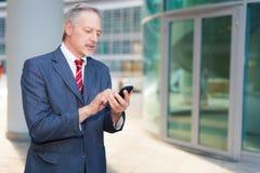 Uomo di affari che per mezzo di uno smartphone Immagini Stock