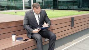 Uomo di affari che prende le note su all'aperto di carta archivi video