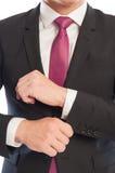 Uomo di affari che ripara la sua manica della camicia Immagini Stock