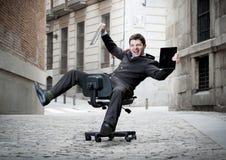 Uomo di affari che rotola in discesa sulla sedia con il computer e la compressa Immagine Stock Libera da Diritti