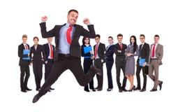 Uomo di affari che salta davanti al suo gruppo di affari Immagine Stock