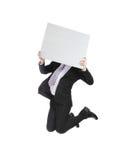 Uomo di affari che salta e che tiene tabellone per le affissioni fotografia stock libera da diritti