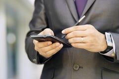 Uomo di affari che scrive con Pen On Phablet Smartphone Fotografie Stock Libere da Diritti