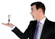 Uomo di affari che sembra colpito sulla piccola donna Fotografia Stock