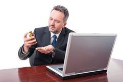 Uomo di affari che sembra sollecitato prendendo le pillole immagine stock