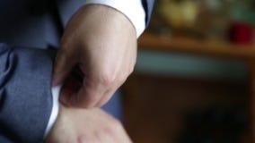 Uomo di affari che si agghinda con le scarpe classiche e eleganti Governi le scarpe d'uso sul giorno delle nozze, legando i pizzi video d archivio