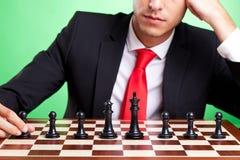 Uomo di affari che si leva in piedi davanti all'allineamento di scacchi Fotografie Stock Libere da Diritti