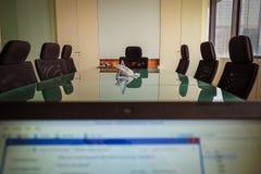 Uomo di affari che si nasconde dietro il computer portatile nel primo perso di riunione Immagini Stock Libere da Diritti