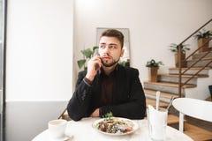 Uomo di affari che si siede ad un ristorante con insalata e una tazza di caffè sulla tavola, parlante sullo smartphone fotografie stock