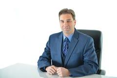 Uomo di affari che si siede ad una tavola e ad una sedia Fotografie Stock