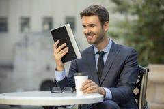 Uomo di affari che si siede alla caffetteria che legge un dispositivo della compressa Fotografia Stock Libera da Diritti