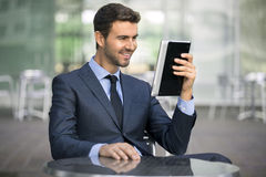 Uomo di affari che si siede alla caffetteria che legge un dispositivo della compressa Fotografie Stock