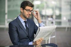 Uomo di affari che si siede alla caffetteria con un giornale Fotografia Stock Libera da Diritti