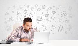 Uomo di affari che si siede alla tavola con le icone disegnate a mano di media Fotografia Stock