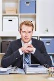 Uomo di affari che si siede allo scrittorio Fotografie Stock