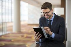 Uomo di affari che si siede leggendo un dispositivo della compressa Fotografia Stock