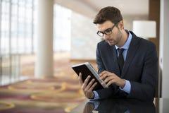 Uomo di affari che si siede leggendo un dispositivo della compressa Fotografie Stock