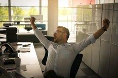 Uomo di affari che si siede nell'ufficio e che allunga sulla sedia Bu stanchi Fotografia Stock