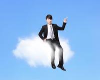 Uomo di affari che si siede su una nuvola Fotografia Stock Libera da Diritti