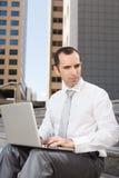 Uomo di affari che si siede sui punti facendo uso del computer portatile Immagini Stock