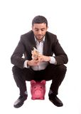 Uomo di affari che si siede sul porcellino salvadanaio che conta gli euro dei soldi Immagine Stock